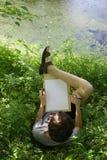 El muchacho del artista del adolescente hace el bosquejo del proyecto del lago de la charca en el bosque Imagen de archivo libre de regalías