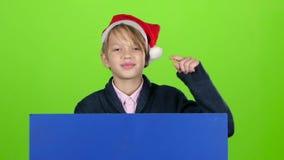 El muchacho del joven apareció de detrás puntos de un cartel del azul a sus dedos índices Pantalla verde Cámara lenta almacen de video