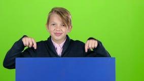 El muchacho del niño aparecía de detrás un cartel azul mirarlo las demostraciones como la ocultación otra vez Pantalla verde Cáma almacen de metraje de vídeo