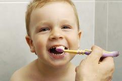 El muchacho del niño aplica los dientes con brocha fotos de archivo libres de regalías