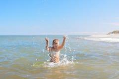 El muchacho del niño asperja el agua en un mar Imagen de archivo