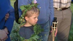El muchacho del niño con la flor y las plantas coronan en el acontecimiento del día de fiesta del pleno verano metrajes