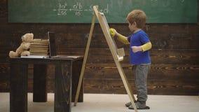 El muchacho del niño dibuja en la pizarra Peque?o colegial que limpia la pizarra De nuevo a mensaje de la escuela contra la escri metrajes
