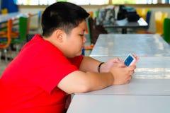 El muchacho del niño es adictivo jugando la tableta y los teléfonos móviles Imagen de archivo libre de regalías