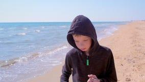 El muchacho del niño está activando caminando en la playa del arena de mar poco corredor en deporte al aire libre almacen de metraje de vídeo