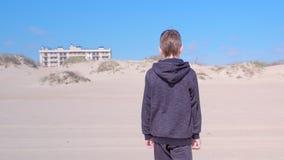 El muchacho del niño está caminando en la playa de la arena a las dunas de arena detrás ve actividades del aire libre metrajes