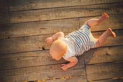 El muchacho del niño recién nacido A, de un año, está mintiendo en su estómago en un muelle de madera, un embarcadero en ropa ray Imágenes de archivo libres de regalías