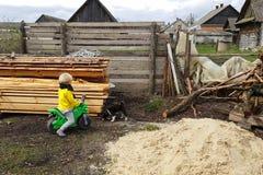 El muchacho del nieto se divierte en su hogar de la abuela en el pueblo, jugando con un perrito Fotografía de archivo libre de regalías