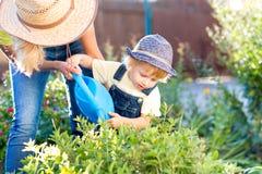 El muchacho del niño ayuda a mimar al trabajo en el jardín Imagen de archivo
