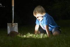 El muchacho del niño ha desenterrado un tesoro en la hierba Foto de archivo libre de regalías