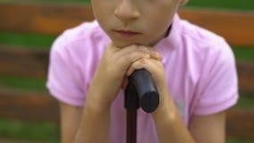 El muchacho del trastorno con el bastón siente solo, no tiene ningún amigo, vida difícil para discapacitado metrajes