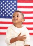 El muchacho delante de la bandera americana con entrega el corazón Imagen de archivo libre de regalías