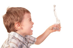 El muchacho derrama el agua del vidrio Imagen de archivo libre de regalías