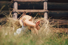 El muchacho descalzo duerme en la hierba cerca de escalera en pajar Imagenes de archivo