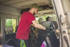 El muchacho descarga objetos de la furgoneta foto de archivo