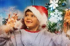 El muchacho detrás adorna la ventana antes de la Navidad Imagen de archivo
