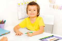 El muchacho dibuja con la pluma durante sentarse en la tabla Fotografía de archivo