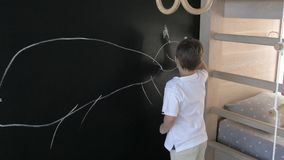 El muchacho dibuja en la pared de la pizarra en el cuarto de niños el niño dibuja en la pared negra con tiza almacen de metraje de vídeo