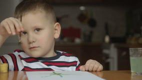 El muchacho dibuja la borla y las pinturas Fondo agradable almacen de metraje de vídeo