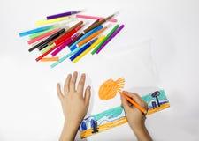 El muchacho dibuja un sistema de la imagen del marcador multicolor Fotografía de archivo