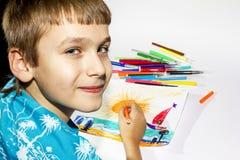 El muchacho dibuja un sistema de la imagen del marcador multicolor Imagen de archivo