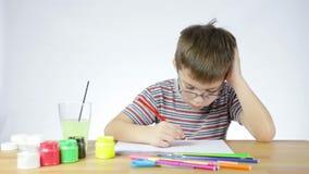 El muchacho dibuja una imagen de un lápiz almacen de video