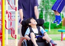 El muchacho discapacitado en silla de ruedas que goza mirando a amigos juega en el par foto de archivo libre de regalías