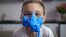 El muchacho divertido adorable con la cara cubrió el limo azul almacen de metraje de vídeo