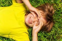 El muchacho divertido con las manos en cara en vidrios forma Fotos de archivo libres de regalías
