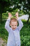 El muchacho divertido con los cuernos de los dientes de león foto de archivo