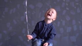El muchacho divertido en ropa azul está jugando con el globo rojo contra la pared gris El niño es feliz en casa almacen de metraje de vídeo