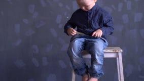 El muchacho divertido en ropa azul está jugando con el globo rojo contra la pared gris El niño es feliz en casa metrajes