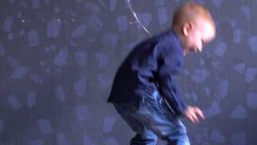 El muchacho divertido en ropa azul está jugando con el globo rojo contra la pared gris El niño es feliz en casa almacen de video