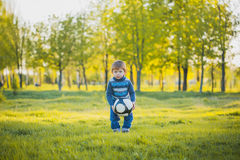 El muchacho divertido está golpeando la bola con el pie en el campo Fotos de archivo libres de regalías