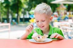 El muchacho divertido lindo feliz está comiendo el helado en café Imágenes de archivo libres de regalías