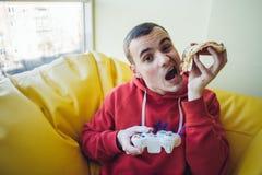 El muchacho divertido que juega a un videojuego en la consola y come la pizza deliciosa Resto del adolescente moderno Fotografía de archivo libre de regalías