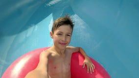 El muchacho divertido va abajo en el tobogán acuático en el parque del agua mira en la cámara fotografía de archivo libre de regalías