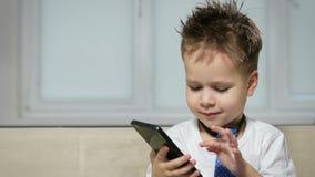 El muchacho divertido y feliz 3-4 años comunica en un teléfono móvil Pequeño hombre de negocios metrajes