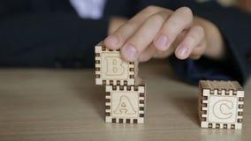 El muchacho dobla los cubos con las letras inglesas almacen de video