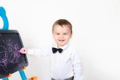 El muchacho drena una tiza en una tarjeta Foto de archivo libre de regalías