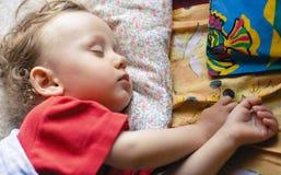El muchacho duerme en las almohadillas varicoloured Foto de archivo