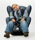 El muchacho duerme en silla auto segura Imagenes de archivo