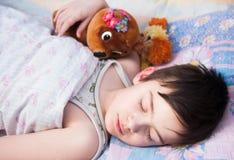 El muchacho duerme en una cama Imagen de archivo