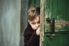El muchacho durante el juego mira fuera de la puerta Imagen de archivo libre de regalías