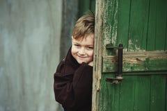 El muchacho durante el juego mira fuera de la puerta Fotos de archivo libres de regalías