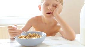 El muchacho durmiente olvidó añadir la leche en su muesli de la mañana metrajes