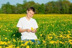 El muchacho el adolescente en un prado floreciente Imágenes de archivo libres de regalías
