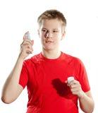 El muchacho el adolescente en una camiseta roja con una botella en manos en un fondo blanco Foto de archivo libre de regalías
