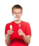 El muchacho, el adolescente intenta tener un afeitado y es la primera vez confuso Imagenes de archivo
