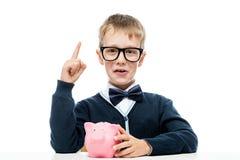El muchacho elegante con una hucha subió con una idea Foto de archivo libre de regalías